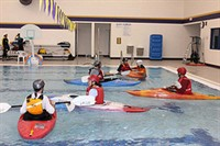 Students in boats in the pool
